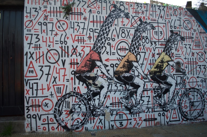 Giraffes riding bicycles over a collaboration piece