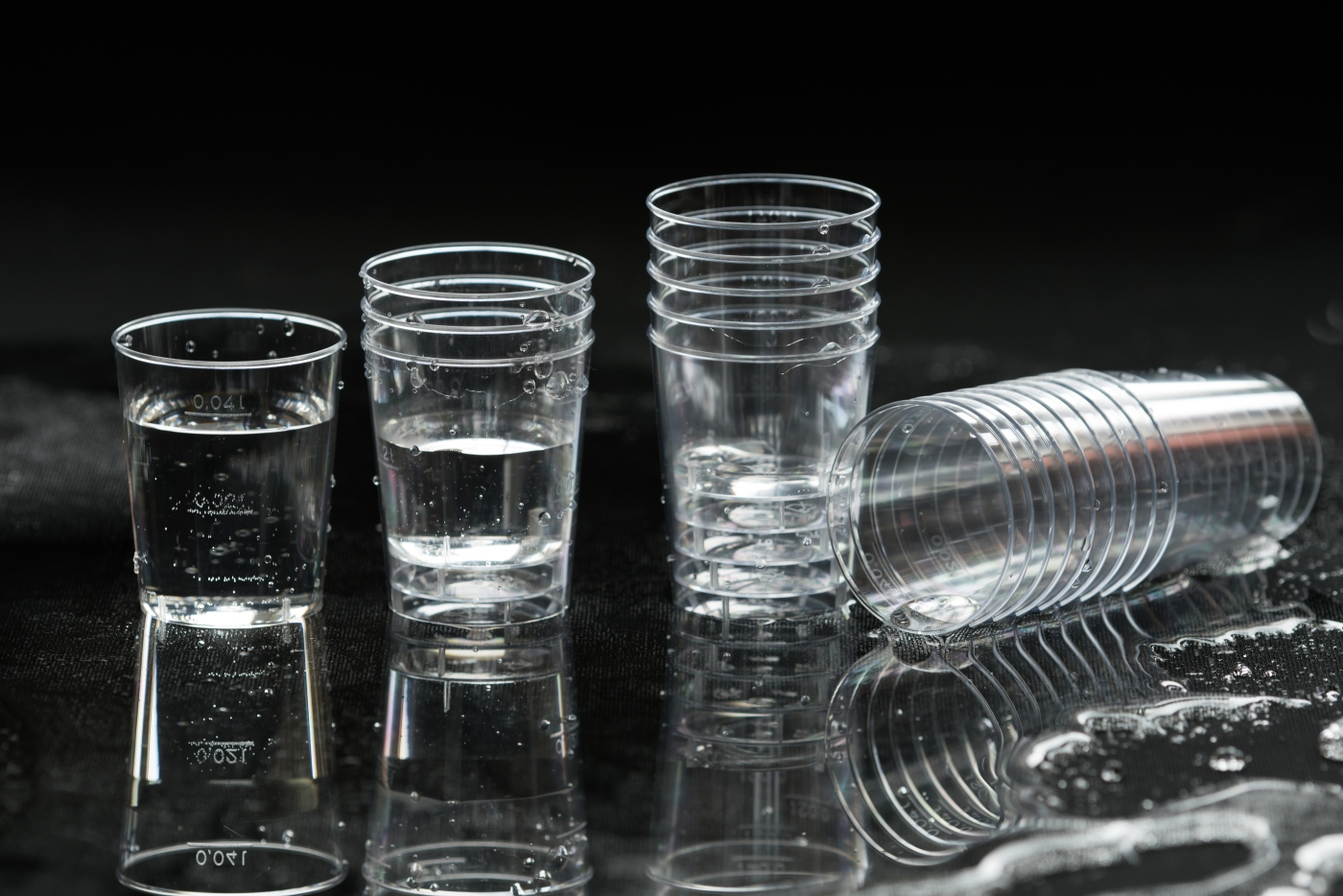 The disposable clear plastic cups to 40 ml with graduation to receive small portions of beverages water and other liquids. Close-up on a black background with blur cups in the background jet of water being poured into a glass pure water in the cup